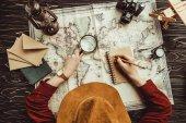 Fotografie letecké snímky žena dělat poznámky na notebook s prázdné obálky, mapa a Fotografie fotoaparát na dřevěný povrch