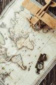 pohled shora mapy, dřevěná hračka letadlo a kompas na tmavý dřevěný povrch