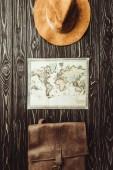 Fotografie pohled shora uspořádány klobouk, mapu a pytel na tmavý dřevěný povrch