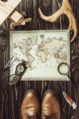 pohled shora cestování nastavení mapy, boty, kompas, zvětšovací sklo a dekorativní rohy na tmavý dřevěný povrch