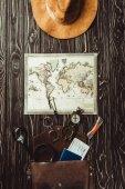 vista superiore di impostazione con il cappello di viaggio, mappa, borsa con occhiali da vista, bussola, passaporto e biglietto su superficie di legno scuro