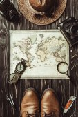 top view of travel setting with straw hat, map, shoes, compass, magnifying glass and photo cameras on dark wooden surface