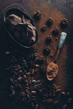 top view of delicious chocolate pieces, cocoa beans and spoon with cocoa powder on dark surface