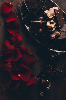 top view of beautiful red rose petals and pieces of gourmet chocolate with nuts