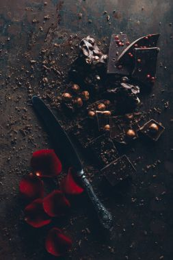 top view of delicious chocolate pieces with nuts, vintage knife and red rose petals on dark surface