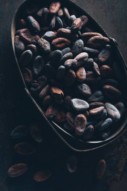close-up view of delicious cocoa beans on dark surface