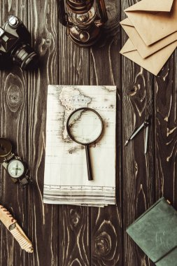 flat lay with arrangement of map, magnifying glass, envelopes, retro photo camera and notebook on dark tabletop