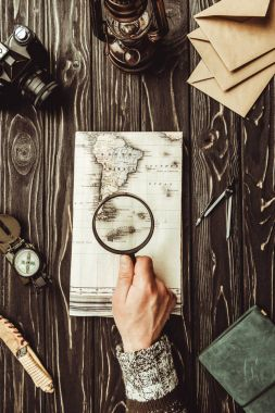 cropped shot of man with magnifying glass at wooden tabletop with map, compass and photo camera