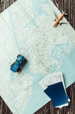 flat lay with map, toys, passports and tickets on dark wooden tabletop