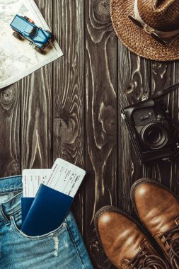 flat lay with denim pants, shoes, straw hat, retro photo camera, passports with tickets on dark wooden tabletop