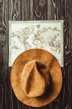 top view of arranged hat and map on wooden tabletop