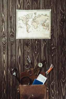 top view of travel setting with map, bag with magnifying glasses, passport and ticket on dark wooden surface