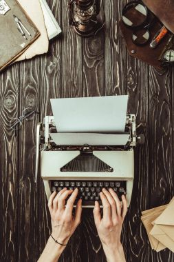 partial view of writer typing on typing machine with blank envelopes and magnifying glasses  on wooden tabletop