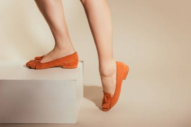 cropped image of female legs in stylish slipper shoes on beige background