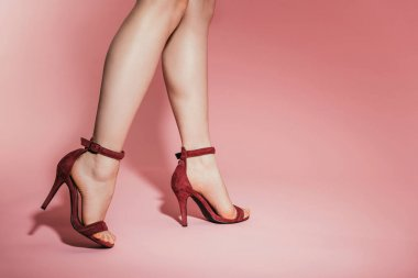 cropped image of woman legs in stylish high heeled sandals on pink background