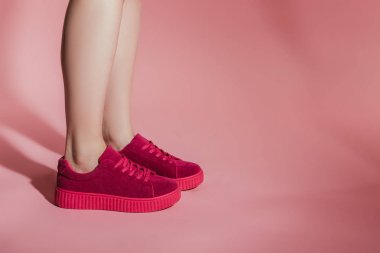 cropped image of woman legs in stylish sneakers on pink background