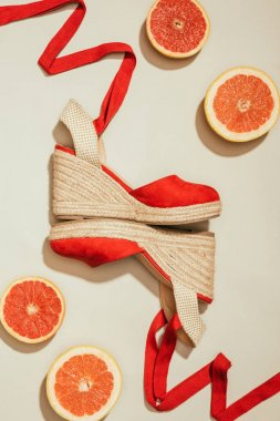 top view of stylish female platform sandals between slices of grapefruits on white background