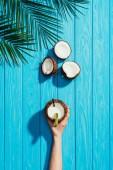 pohled shora lidské ruky a kokosový koktejl, popraskané kokosy a palm listy na tyrkysové dřevěný povrch