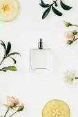 Draufsicht der Glasflasche Parfum mit Blumen umgeben und Apfelscheiben isoliert auf weiss