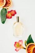 Draufsicht auf eine Flasche aromatischen Parfüms mit Blüten und Grapefruitscheiben isoliert auf weiß