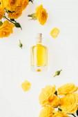 Draufsicht der Glasflasche Parfum und gelbe Rosen isoliert auf weiss