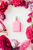 Draufsicht auf eine Flasche aromatischen Parfums, umgeben von Rosenblüten auf weißem Grund
