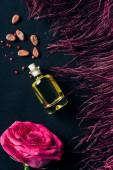 pohled shora na parfém s červeným peřím a růže bud na černém pozadí