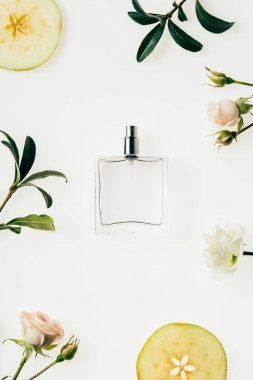 top view of glass bottle of perfume surrounded with flowers and apple slices isolated on white