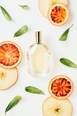 top view of bottle of fresh perfume surrounded with fruits and flowers isolated on white