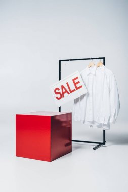 red cube, shirts on hangers and sale sign, summer sale concept