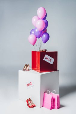 bundle of pink and violet balloons, shopping bags and sale sign, summer sale concept