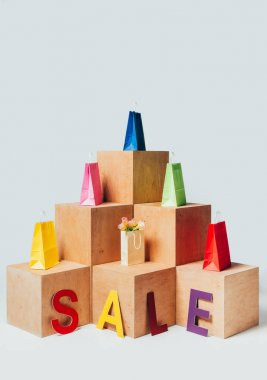 colored shopping bags on wooden stands with sale sign isolated on white, summer sale concept
