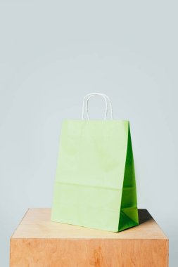 one light green paper bag on wooden stand isolated on white, summer sale concept