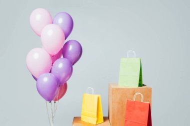 bundle of pink and violet balloons near shopping bags on stands isolated on white, summer sale concept