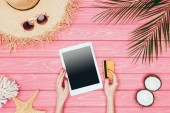 Fotografie cropped shot of woman holding digital tablet with credit card on pink wooden surface