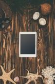 Fotografie pohled shora digitální tabletu na dřevěný povrch s různými tropické cestování atributy