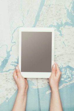 cropped shot of woman using tablet over travel map