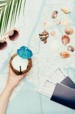 Cropped shot of woman with coconut cocktail and flight tickets on travel map stock vector