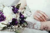 částečný pohled nevěsta v bílých šatech s krásnou svatební kytice