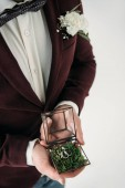 Fotografie partial view of groom in suit with buttonhole and wedding rings in box in hands