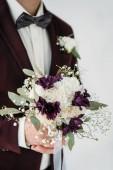 částečný pohled ženich v obleku s krásnou svatební kytice v rukou