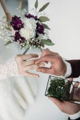 Fotografie partial view of groom wearing wedding ring on bridal finger