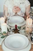 oříznuté shot nevěsty v bílých šatech sedící u stolu servírované s prázdné talíře a pohárky, koncept rustikální svatba