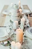 zblízka pohled stylové prostírání svíčky, prázdné pohárky a talíře pro rustikální svatba