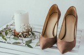Photo close up view of bridal shoes, candle and flowers on grey backdrop