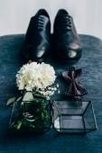 Fotografia Chiuda sulla vista della disposizione delle scarpe degli sposi, farfallino, corpetto e fedi nuziali per matrimonio rustico su priorità bassa blu