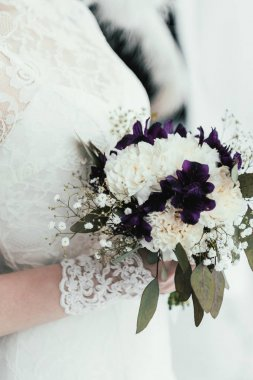 partial view of bride in white dress with beautiful bridal bouquet in hands