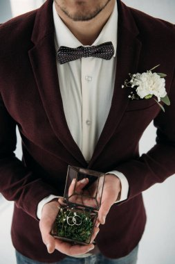 partial view of groom in suit with buttonhole and wedding rings in box in hands