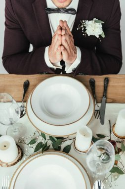cropped shot of groom in suit praying while sitting at served table, rustic wedding concept
