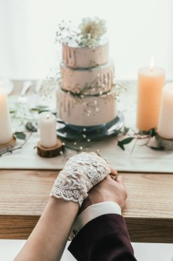 partial view of newlyweds holding hands while sitting at served table with wedding cake, rustic wedding concept